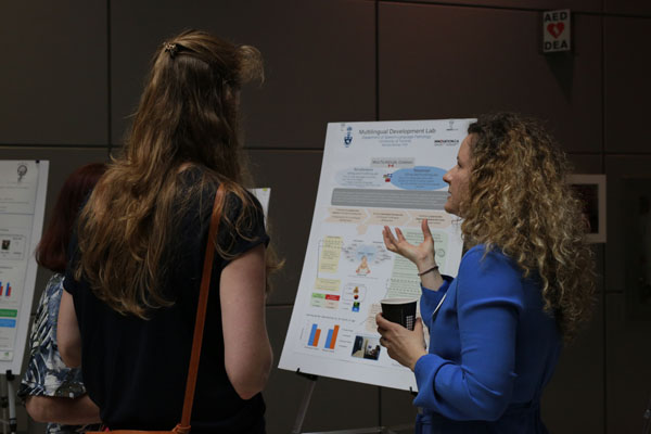 SLP Faculty member discusses her poster with event guest